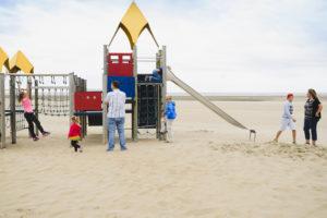 heel mijn gezin op een speeltoestel op het strand, documentaire fotografie