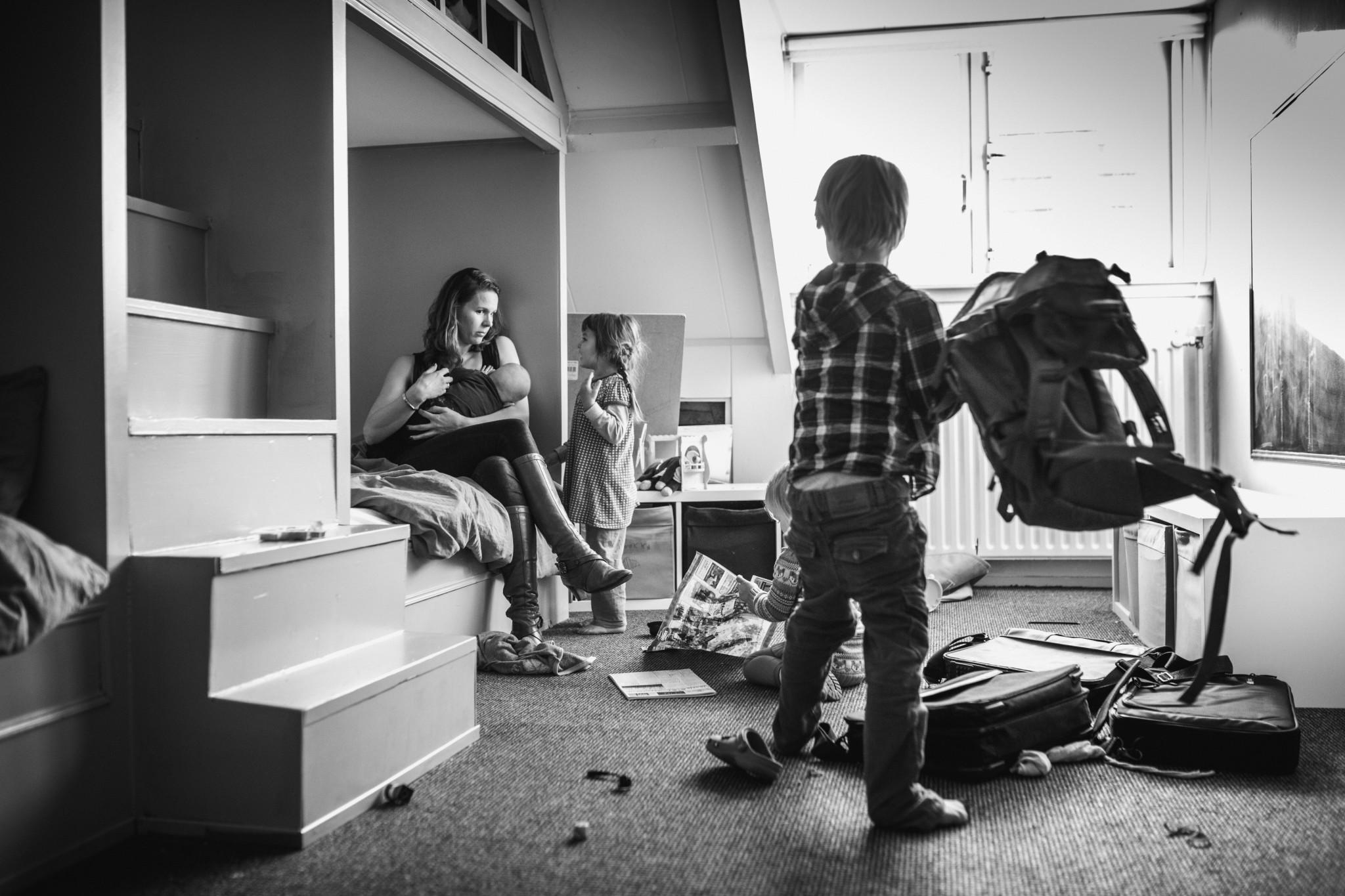 Chaos op zolder, mama voedt de jongste en de andere kinderen spelen daar ook