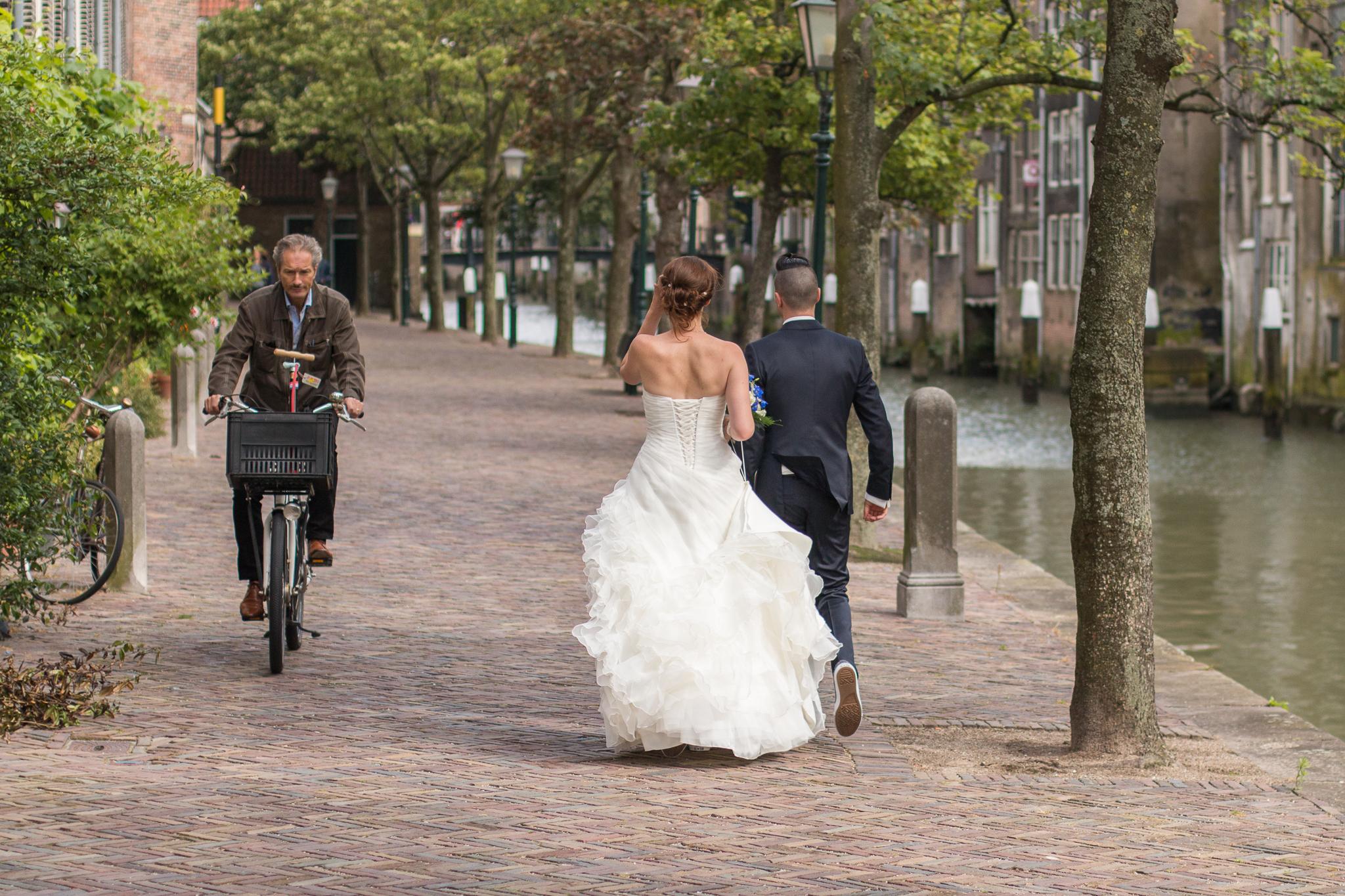 Bruidspaar loopt in Dordrecht en komt man op fiets tegen tijdens fotoshoot, bruidsfotograaf zuid holland