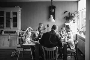 Groot gezin met vijf kinderen eet pannenkoeken, documentaire fotografie