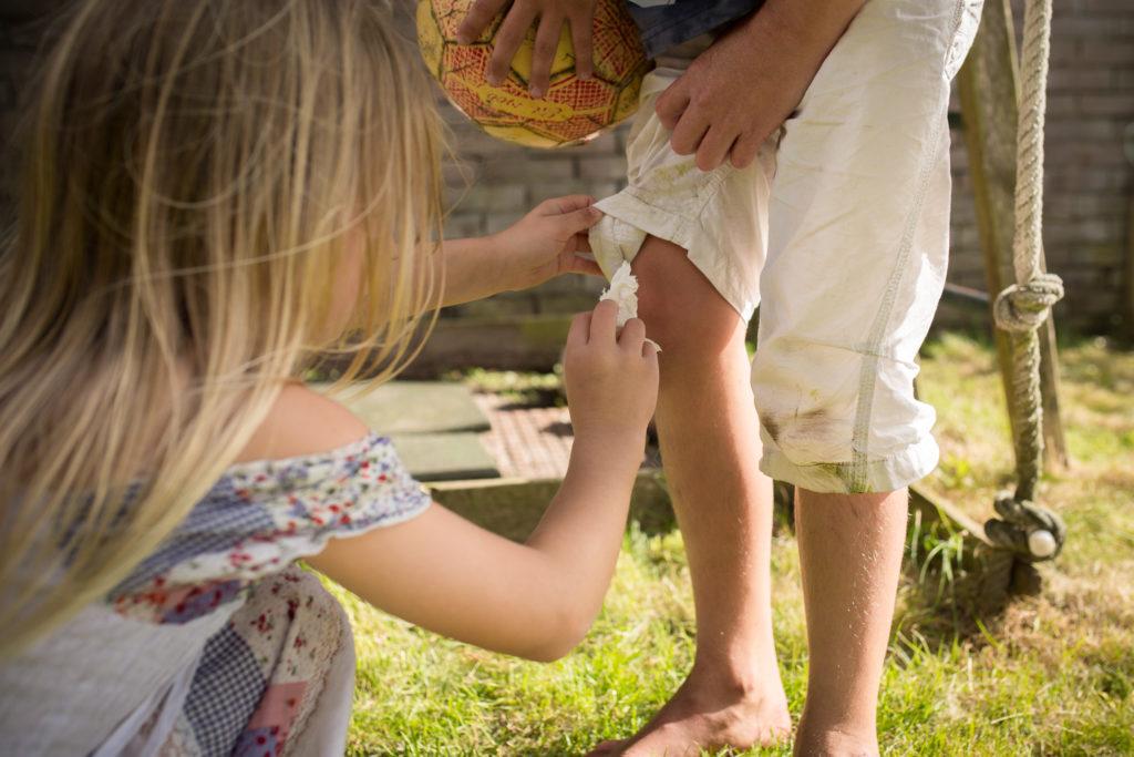 Zusje verzorgt knie van broertje die gevallen is, documentaire fotografie