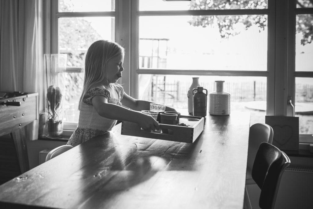 Meisje zet zwaar dienblad op tafel en steekt haar tong uit tijden een day in the life reportage