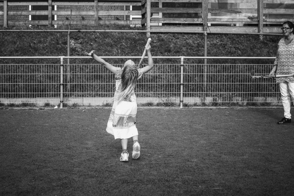 Meisje is blij met haar doelpunt op het hockeyveld, day in the life fotografie