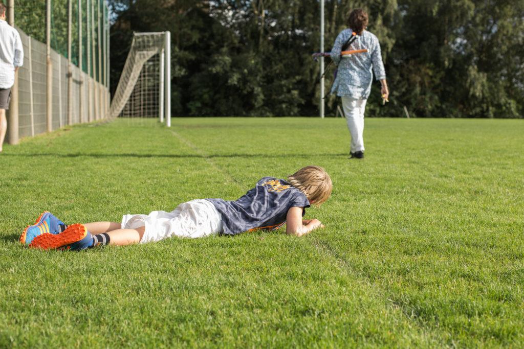 Jongen ligt boos op de grond en wil nog niet naar huis, documentaire fotografie