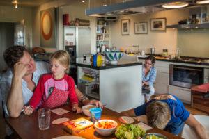 Mama maakt eten terwijl de kinderen met papa een spelletje doen, lifestyle fotografie