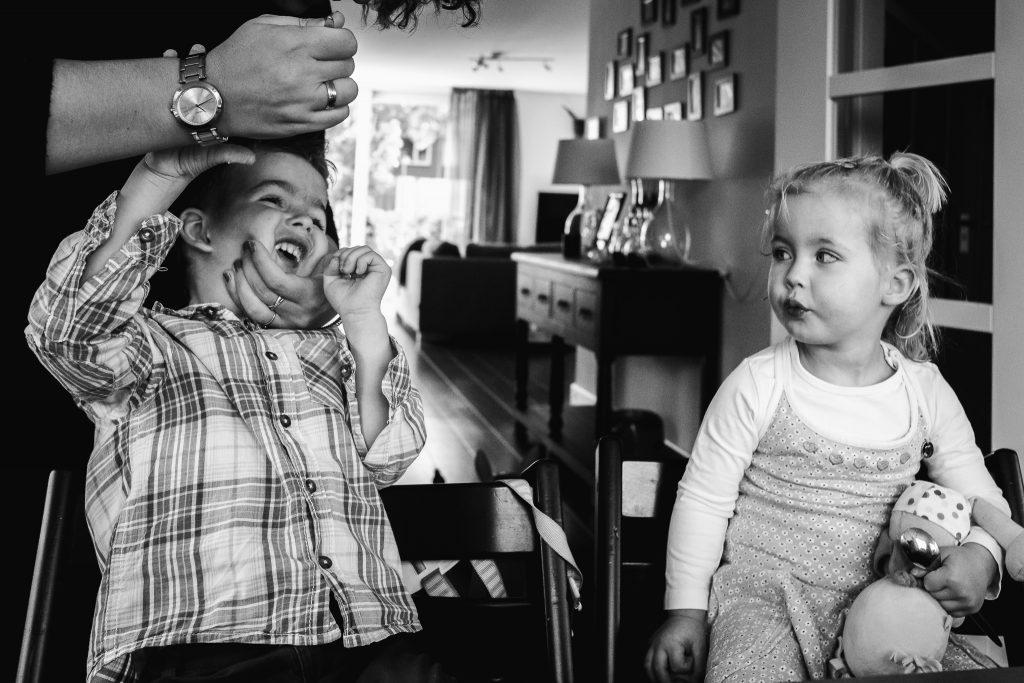 een moeder probeert haar kleuter medicijnen in te laten nemen terwijl het zusje toekijkt