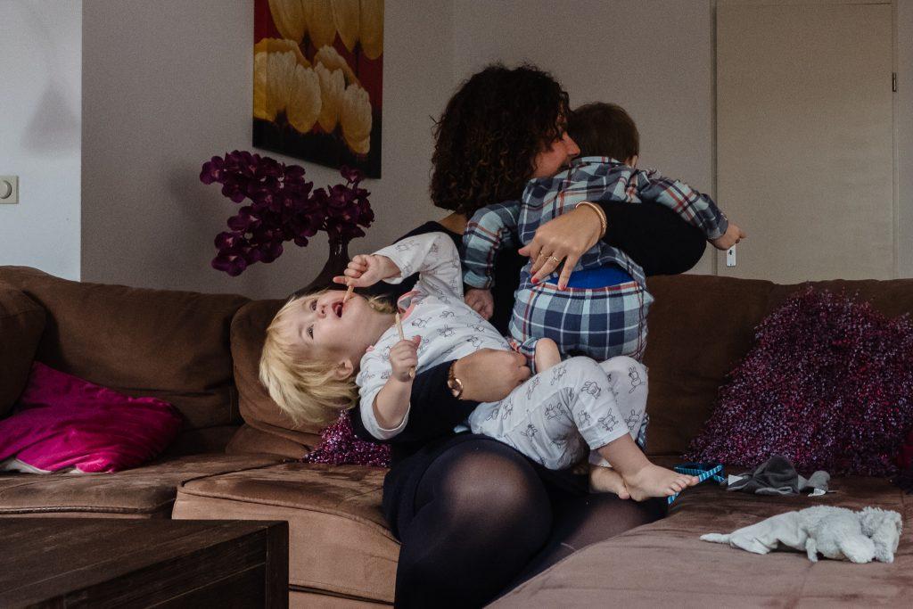 Mama knuffelt haar twee kinderen op de bank