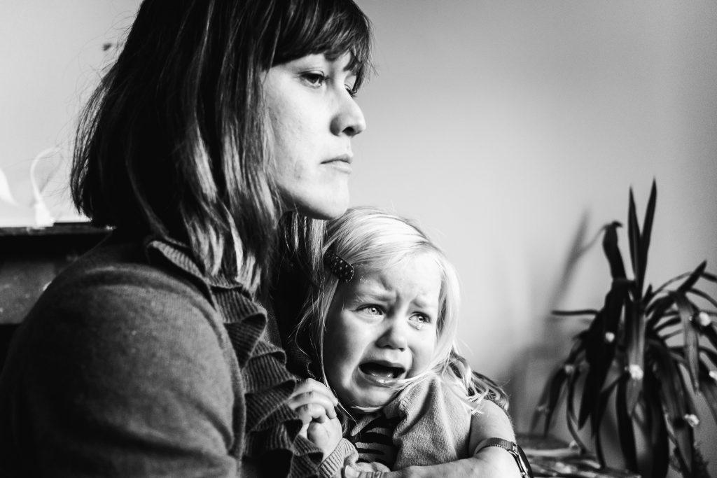 mama kijkt heel boos en streng naar haar zoon terwijl haar dochter huilend op haar schoot zit