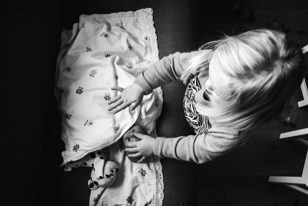 Peuter speelt met haar pop en dekt de pop toe alsof ze in bed ligt