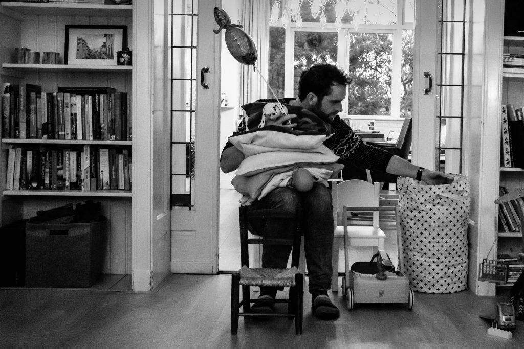 papa zit op een kinderstoeltje en houdt een hele stapel kussens, speelgoed en poppen vast