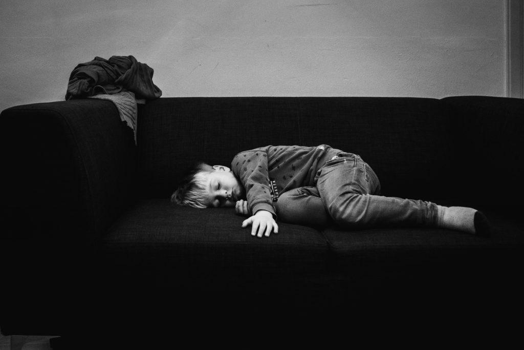 Jongen is in slaap gevallen op de bank