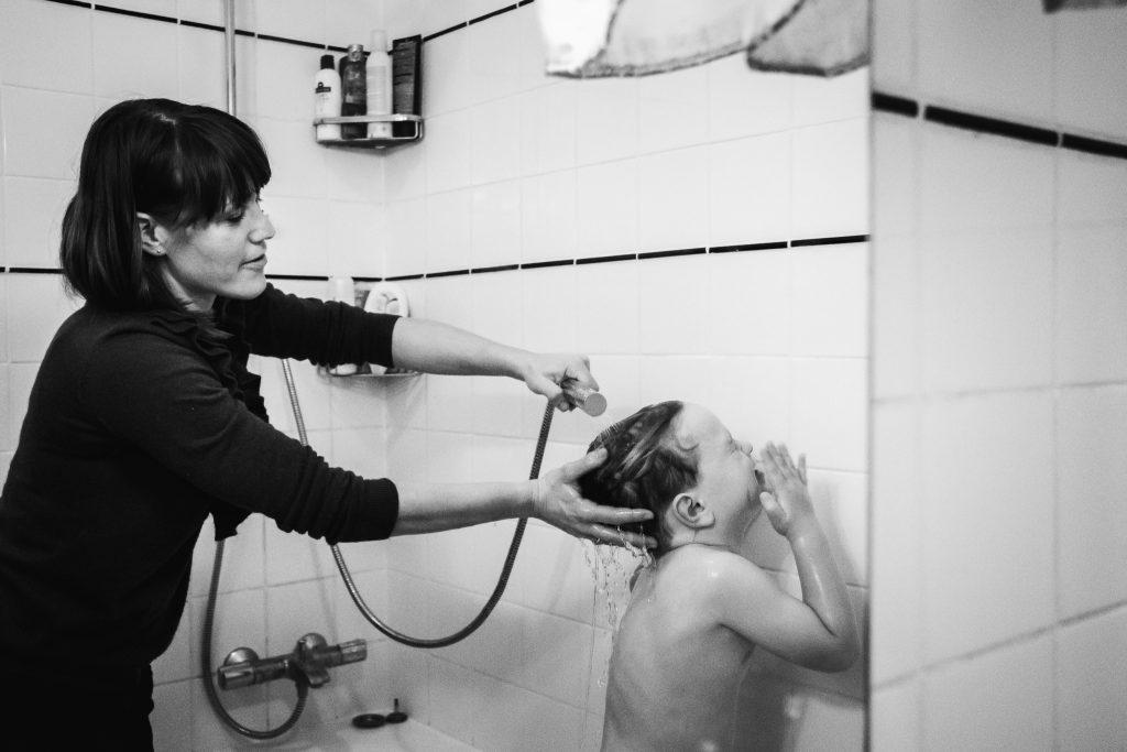 Moeder wast de haren van haar zoon in de douche