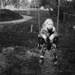Portret van meisje dat op een schommel zit