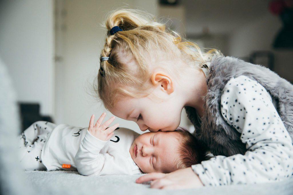 grote zus geeft kleine zus kusje op bed