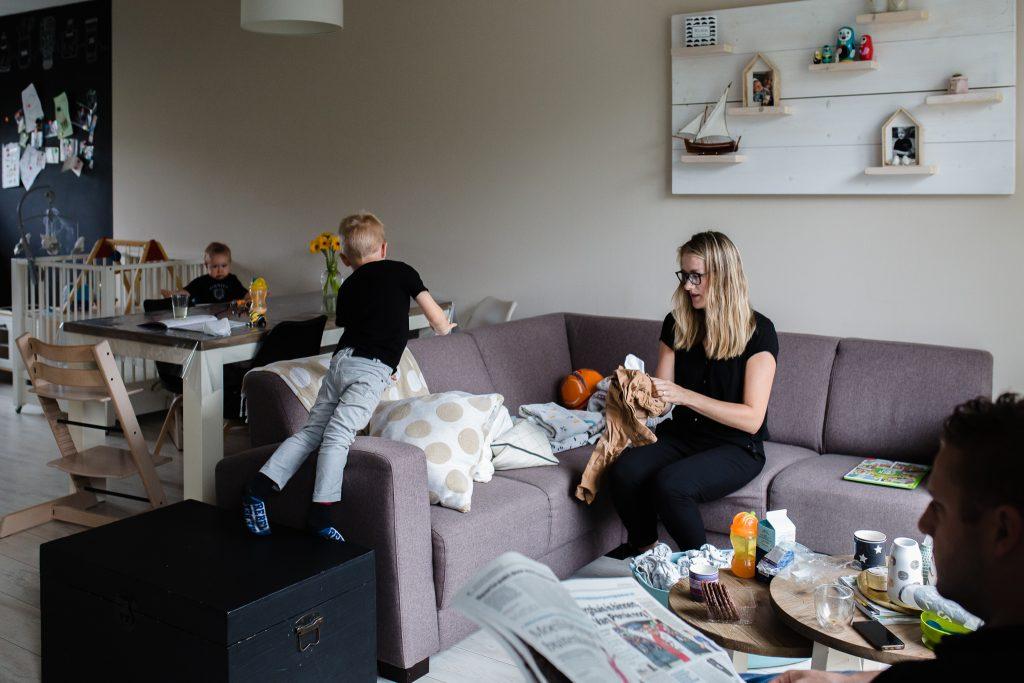 Fotoreportage van een gezin op zaterdagmorgen, papa leest de krant, mama vouwt de was en de kinderen spelen
