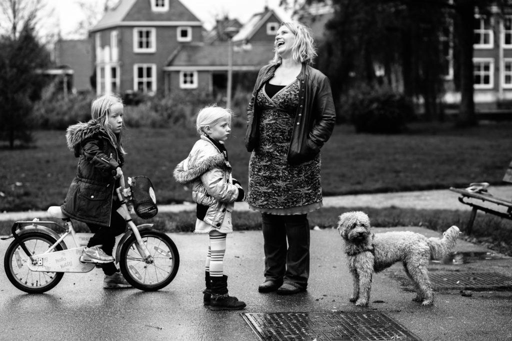 Moeder moet heel hard lachen terwijl de kinderen wat sip kijken tijdens een day in the life reportage