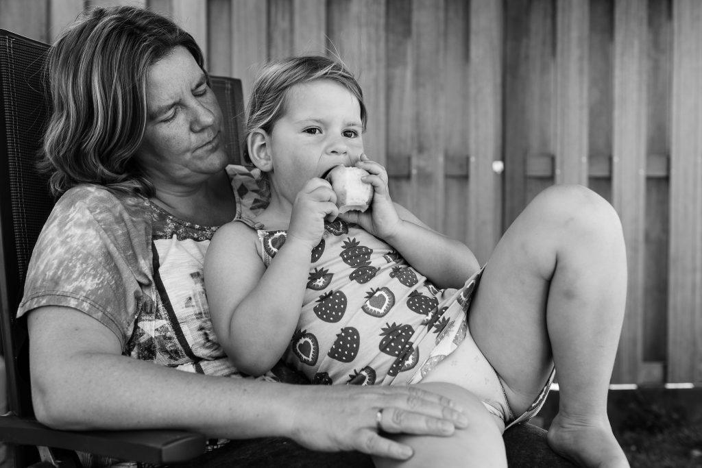 Marjolijn Maljaars, fotograaf, met haar jongste dochter op schoot in de tuin