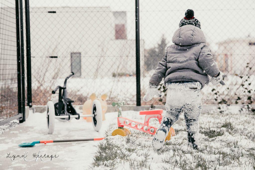 Jongentje speelt in de sneeuw
