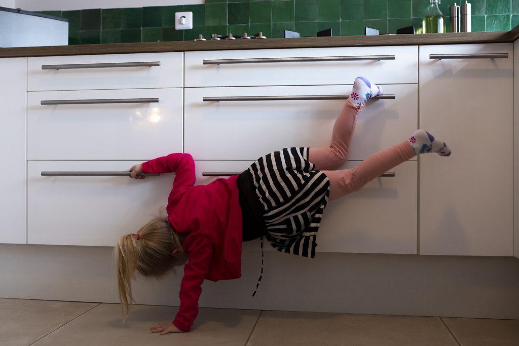 Kindje hangt aan de keukenkastjes, familiefotografie