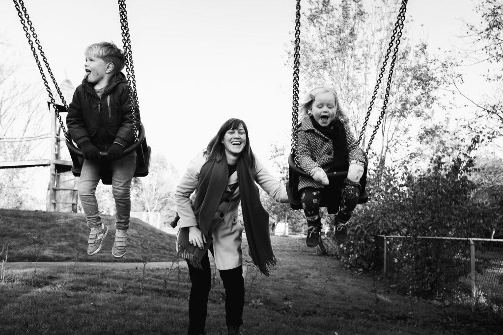 Moeder duwt lachend haar twee kinderen op de schommel