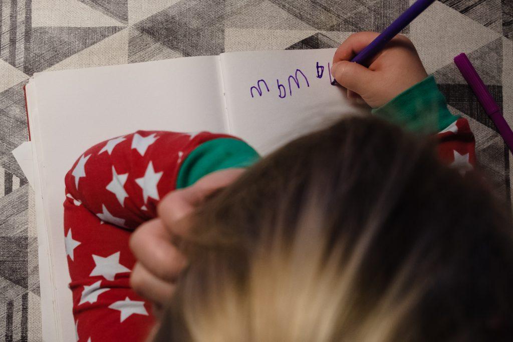 Kleuter wil graag leren schrijven en oefent de letters