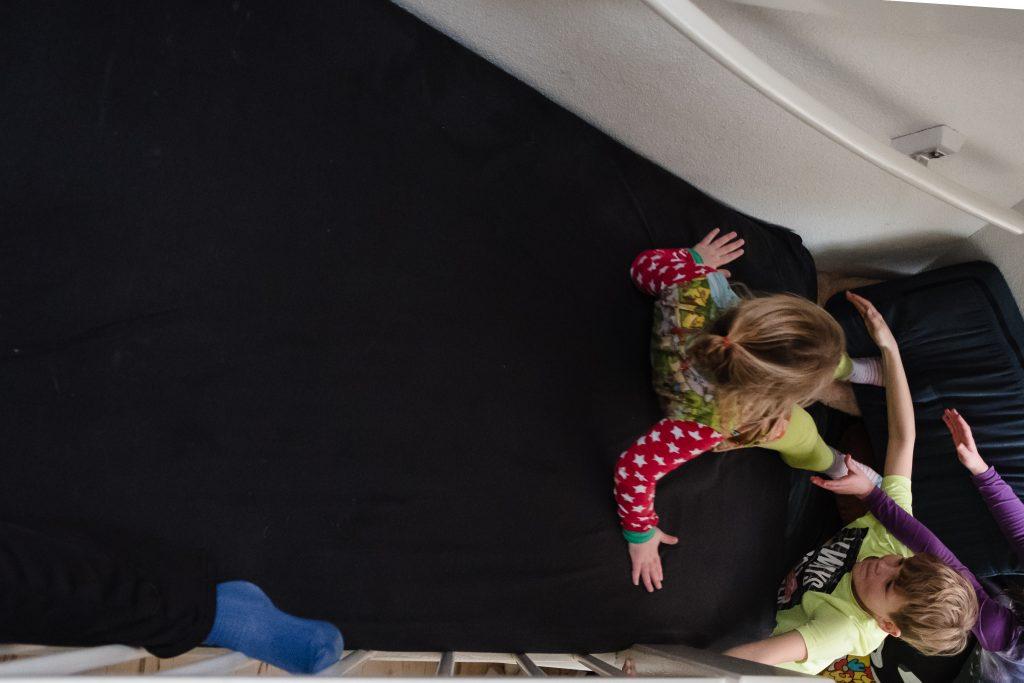 Met matrassen wordt er een glijbaan op de trap gemaakt waarop kinderen naar beneden glijden