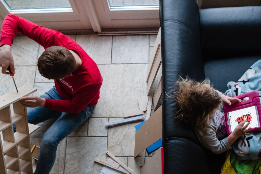 Jongen zet verjaardagscadeau in elkaar terwijl de jarig ziek op de bank op de ipad een spelletje doet