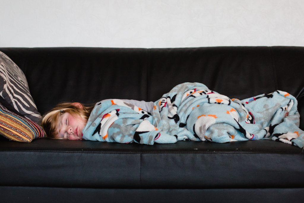 Een ziek meisje slaapt op de bank onder een dekentje