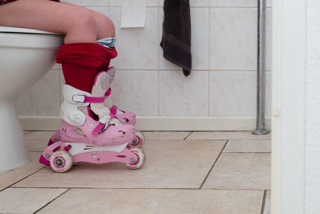 Meisje zit op de wc met haar rolschaatsen nog aan