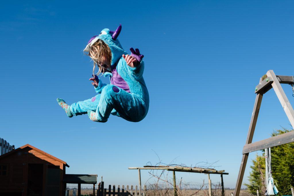 Meisje met een monster verkleedpak springt hoog in de lucht op een trampoline
