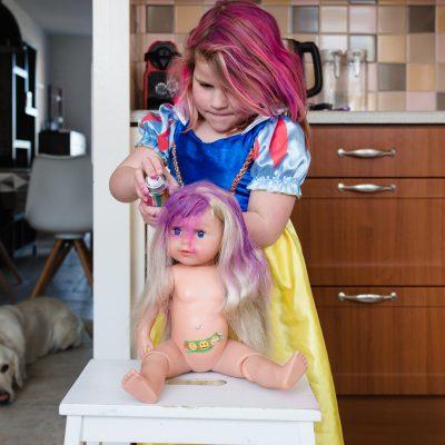 Meisje verkleed als sneeuwwitje met rose haar verft bij haar pop ook het haar rose terwijl de hond, golden retriever, toekijkt