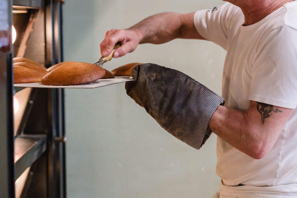 Bedrijfsfotografie voor bakker, zakelijke fotografie voor op de website door maljaars fotografie. Bakker haalt eierkoeken uit de oven