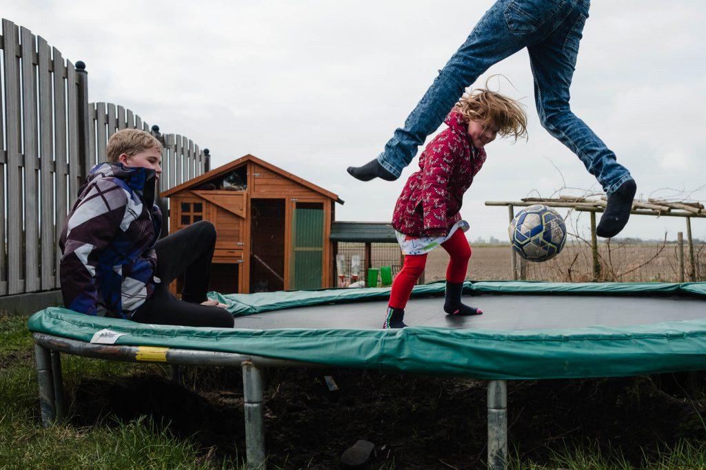 kinderen spelen buiten op de trampoline, documentaire familiefotografie