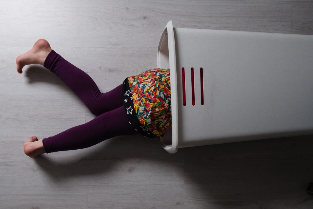 meisje ligt met haar halve lichaam in een wasmand, familie fotografie