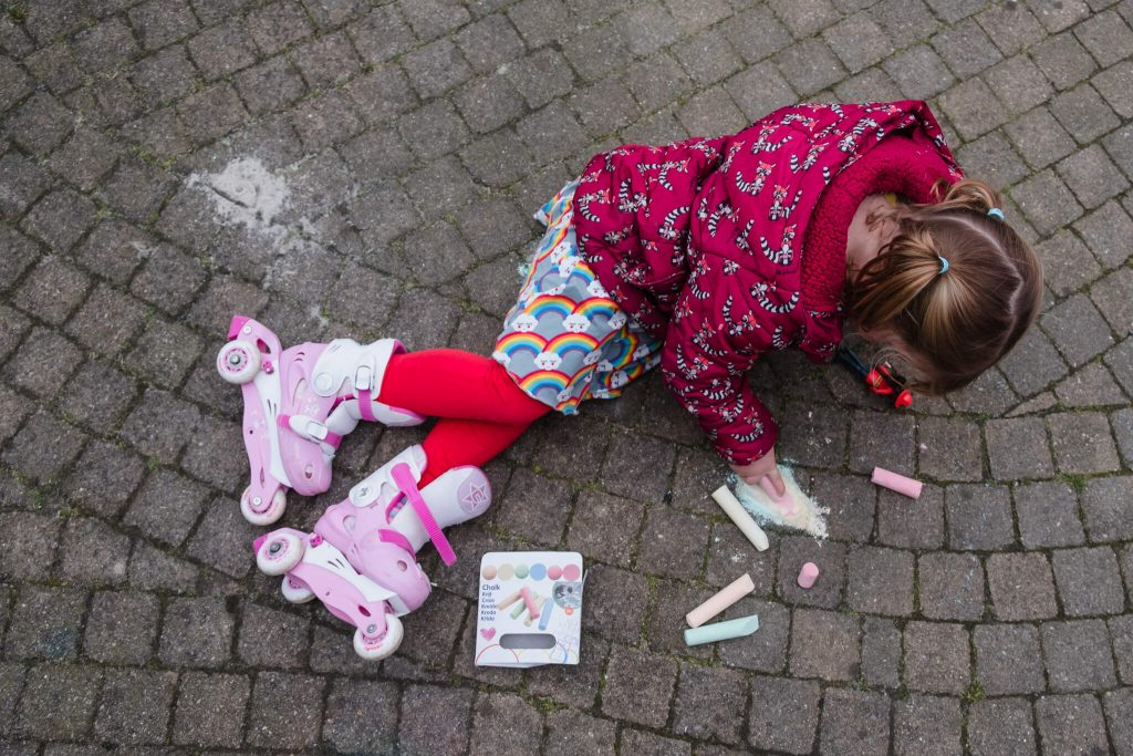 meisje met rolschaatsen aan kleurt met stoepkrijt op de grond