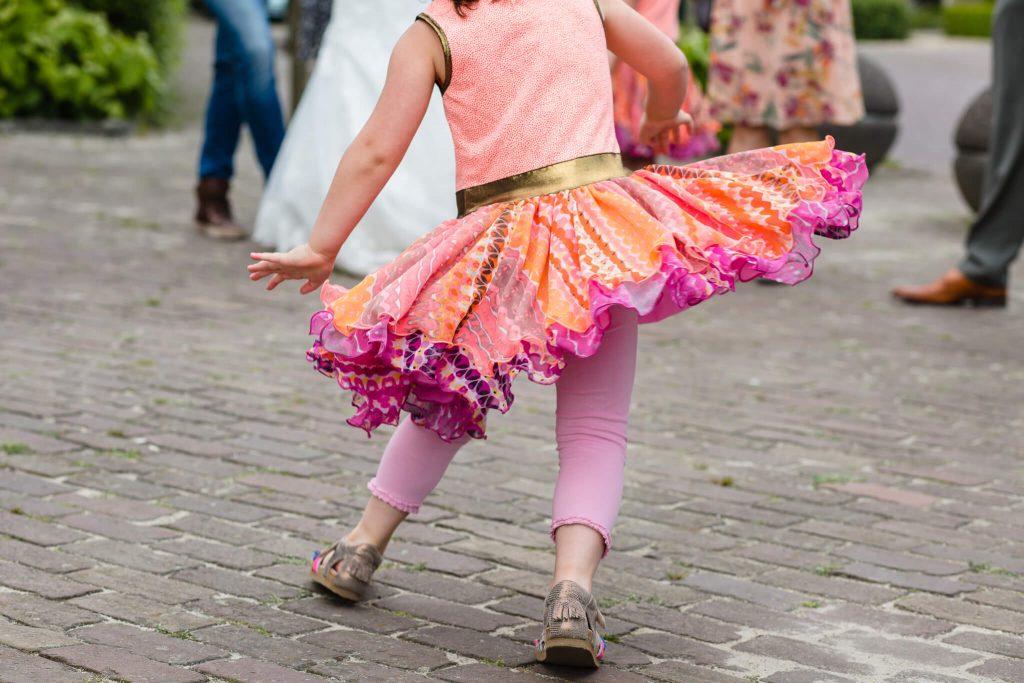 Meisje danst met een draairok op een bruiloft in Brabant