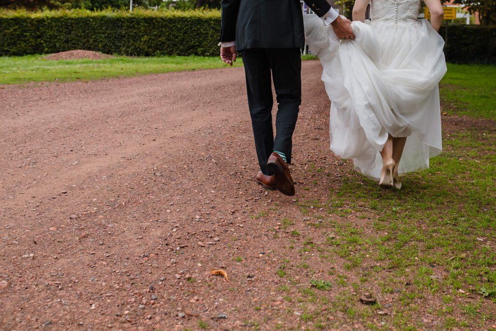 Bruidegom tilt jurk van bruid op zodat hij niet vies wordt, lommerrijk Rotterdam
