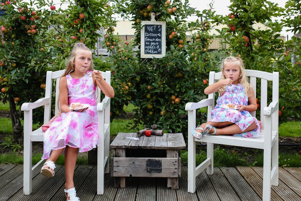 Twee kinderen genieten van de bruidstaart op de bruiloft in de boomgaard