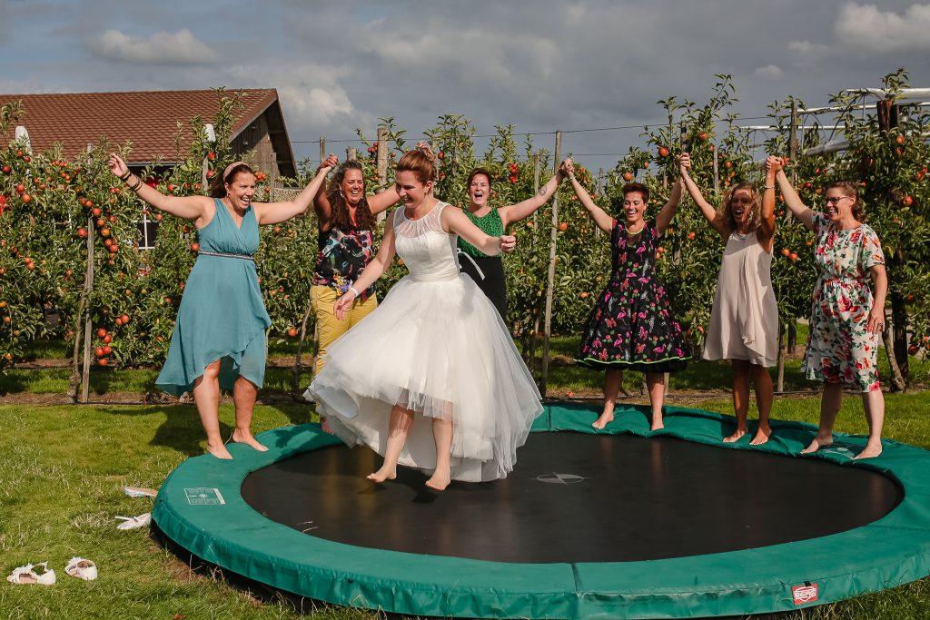 Bruid springt op de trampoline omringd door haar vriendinnen
