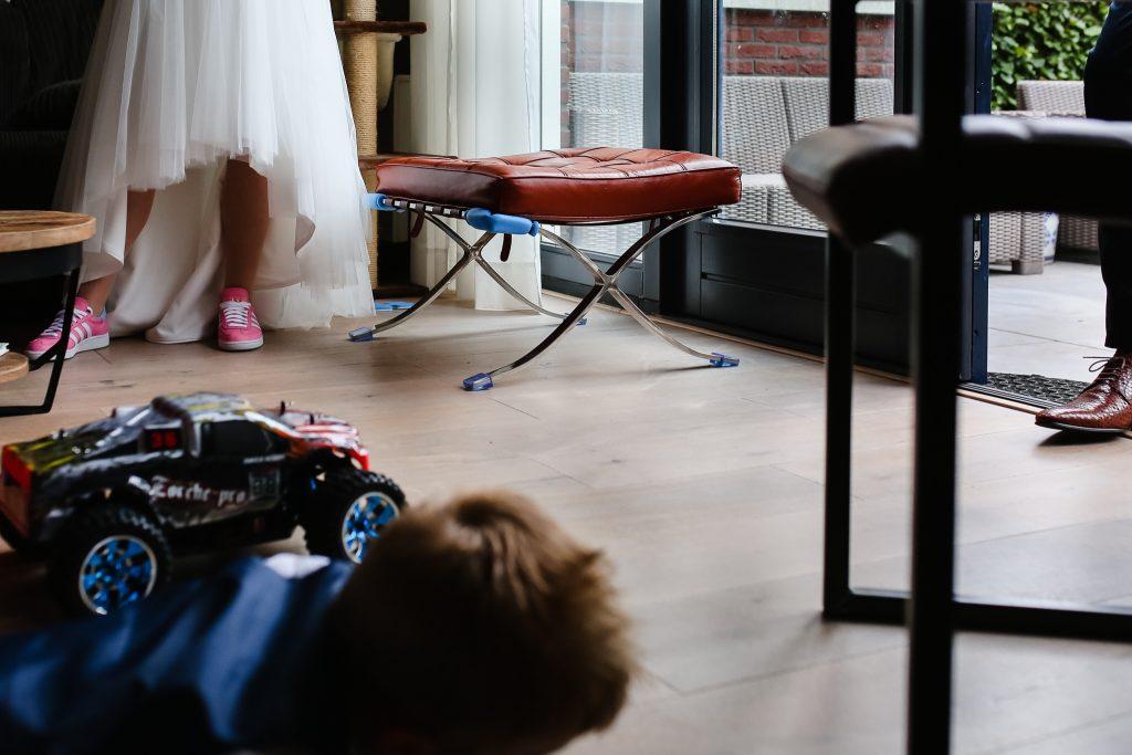 Zoontje speelt op de grond, schoenen van bruid en bruidegom staan er bij, journalistieke bruidsfotografie