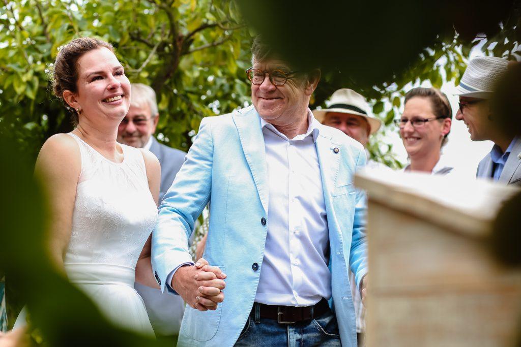 Vader geeft de bruid weg vlak voor de trouwceremonie begint in de boomgaard, trouwen in de boomgaard