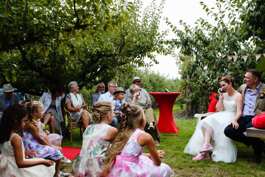 Bruid en moeder van de bruid in tranen tijdens de ceremonie tijdens het trouwen in de boomgaard