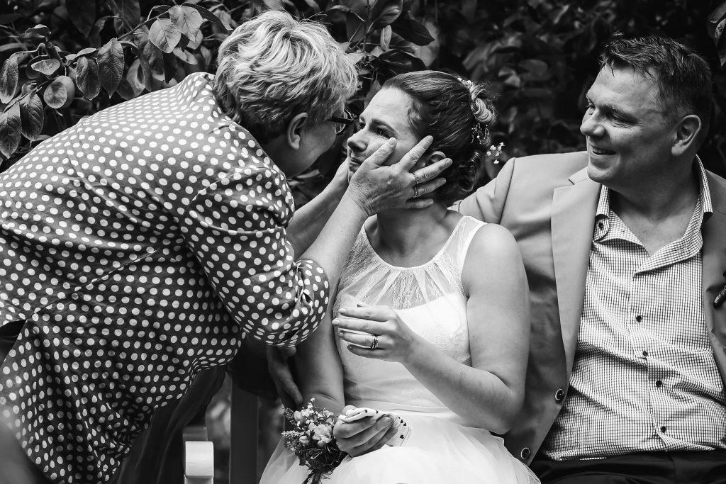 Moeder geeft bruid een dikke knuffel tijdens de ceremonie, trouwen in de boomgaard