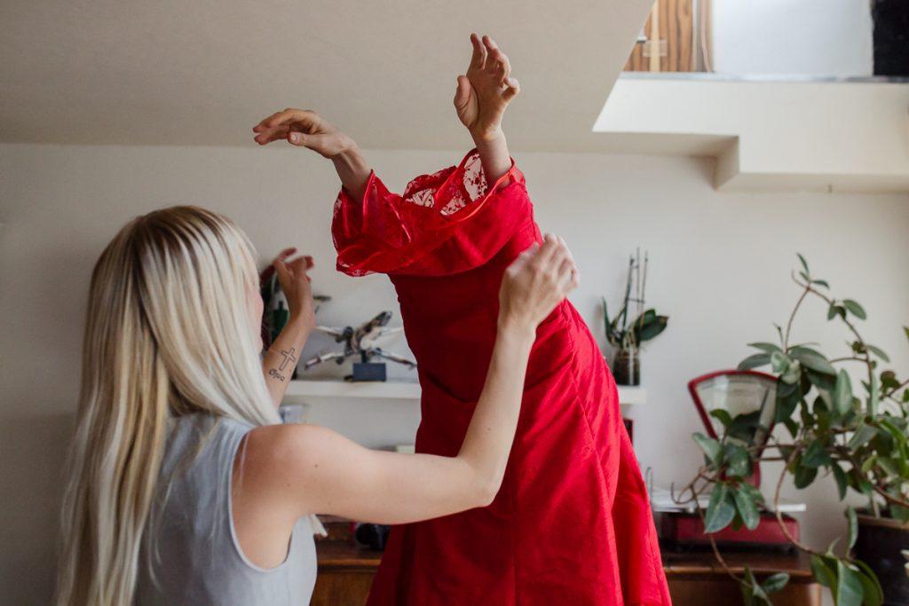 Bruid wordt geholpen bij het aantrekken van haar jurk - Bruidsfotograaf marjolijn maljaars
