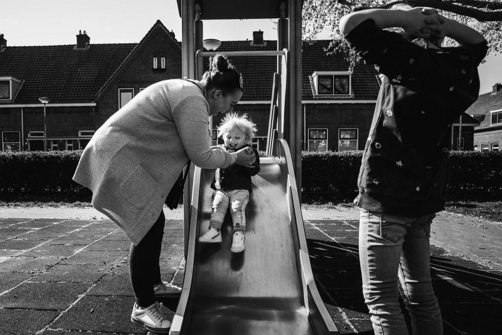 Moeder speelt met haar zonen in de speeltuin tijdens een fotoreportage door Maljaars Fotografie