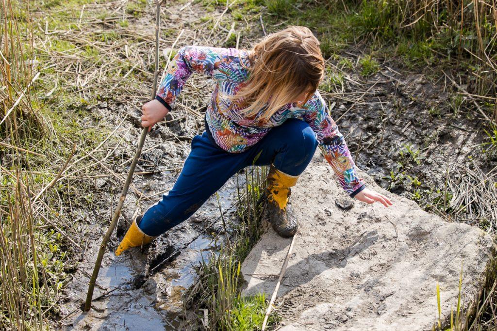 kind speelt in natuurspeeltuin tijdens mini fotosessie